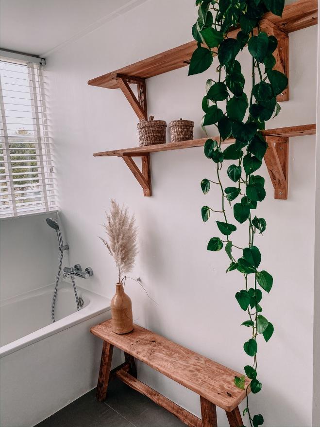 Teakhouten wandplanken en robuust bankje in badkamer